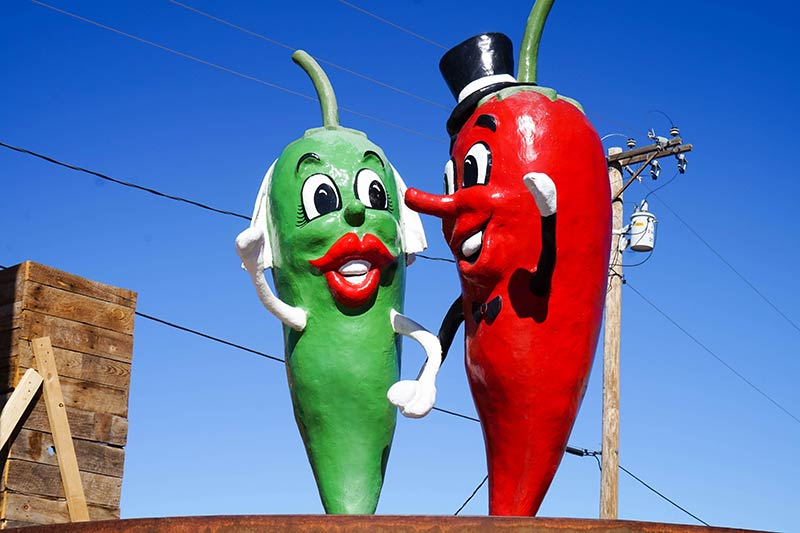 A statue of green and red peppers on a platform with power lines and blue sky behind