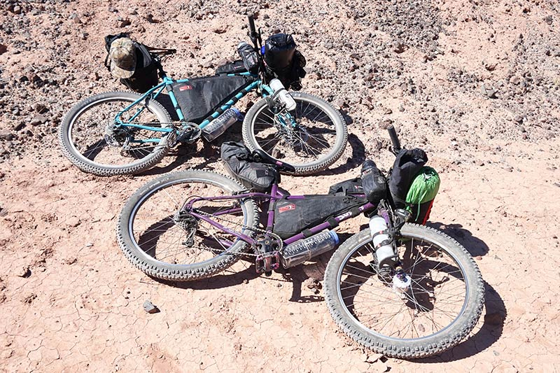 Two Surly bikes loaded with gear, laying on their left side in the sand