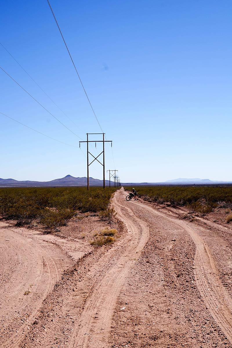 A cyclist standing on a remote sandy, gravel road next to a crossroad with power lines above, and mountains behind them