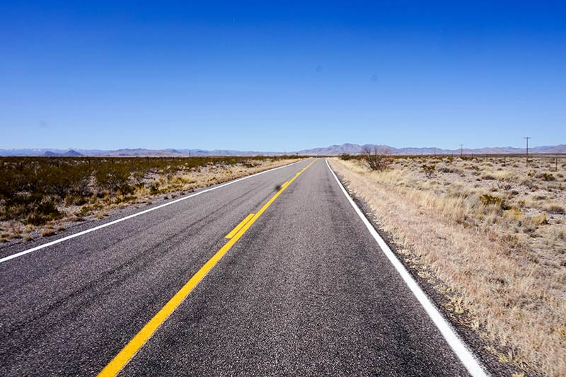 A straight, paved two lane highway in the desert heads into the mountain with blue sky above