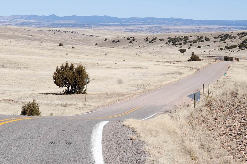 A winding two lane highway plains grass with mountain hills in the distance