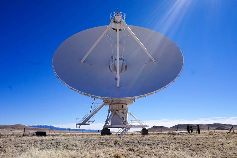 A very large white satellite set up in a field of desert plains on a bright, sunny day