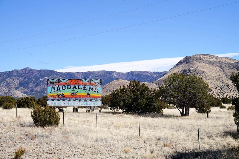 A rainbow colored Magdalena Billboard stands in prairie grass field with trees and mountains in the background