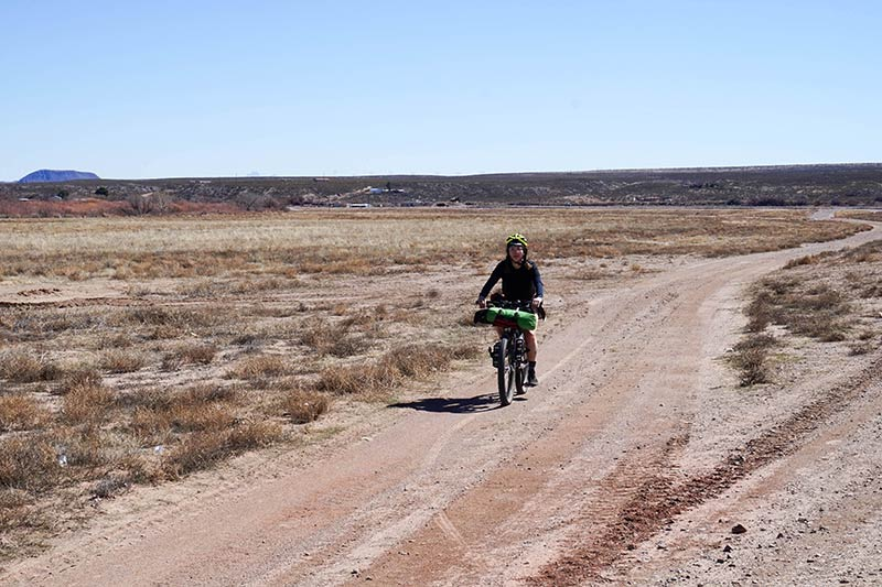 A front view of a cyclist riding on a gravel road in a grassy desert on a clear day