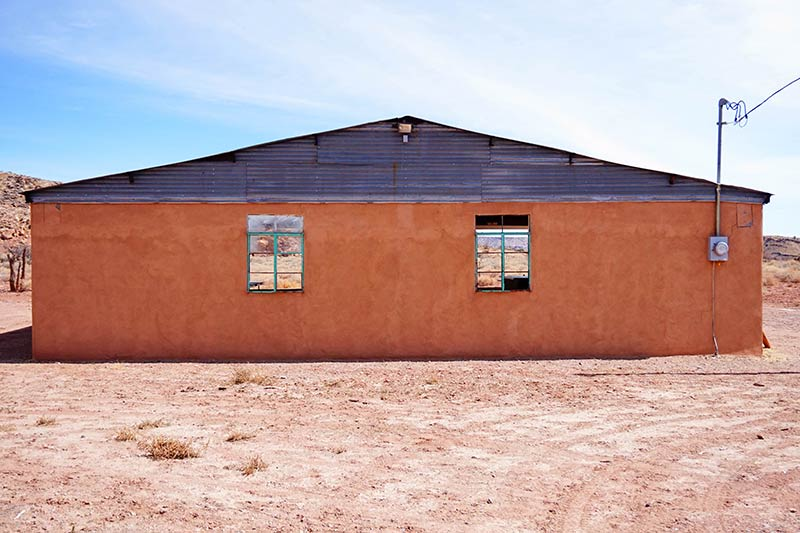 An orange stucco building with a steel roof sits on a sand lot in the desert with blue sky above
