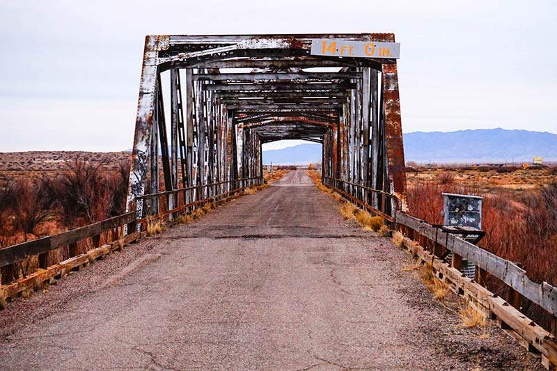 A straight view of a rusty steel bridge,  with a road running through and brush on each side, and mountains ahead