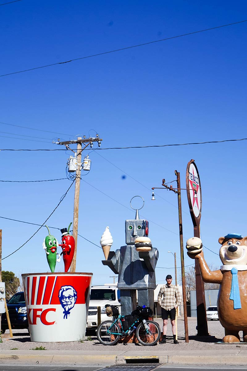 Front view of a cyclist standing with a Surly bike on a sidewalk next to a giant bucket of KFC, robot and yogi the bear