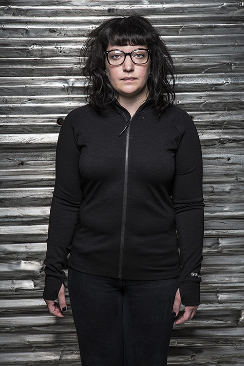 Front view of a person wearing a black wool zip up jacket in front of a corrugated steel wall