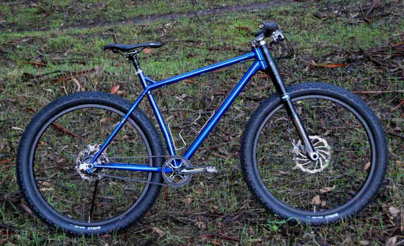 Right profile of a Surly Krampus bike, blue, parked on a grassy hill