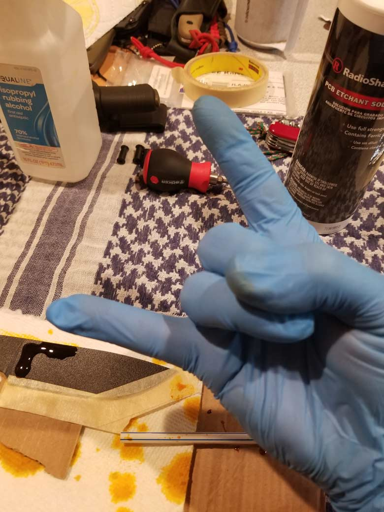 Downward view of hands in nitrile gloves with horns sign, over a bottle of isopropyl alcohol and PCB etchant solution