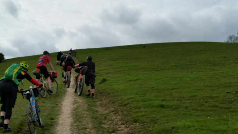 Rear view of cyclists walking their bikes up a hill on a pasture road