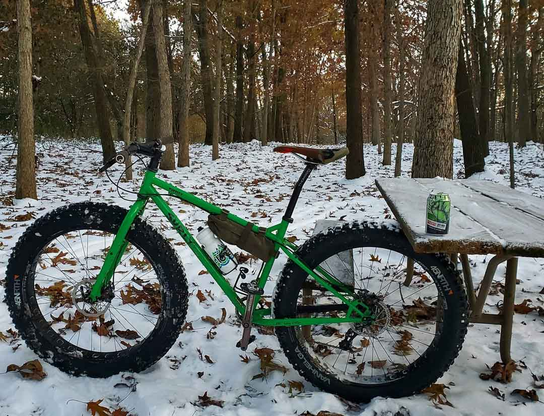 Left profile of a Surly Pugsley fat bike,green, with back tire under a picnic table with beer can on top in snowy woods