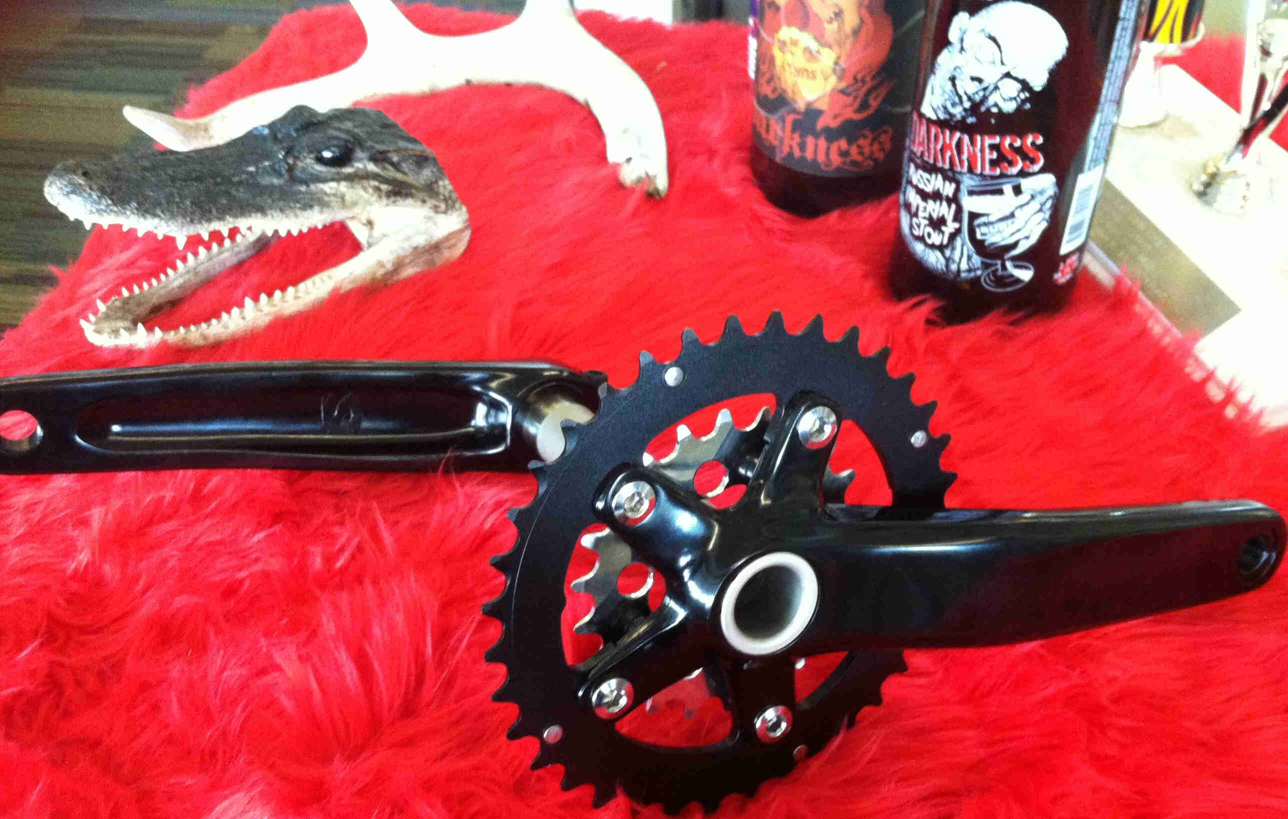 Side view of a Surly O.D bike crankset, on a red table with an alligator head and cans in the background