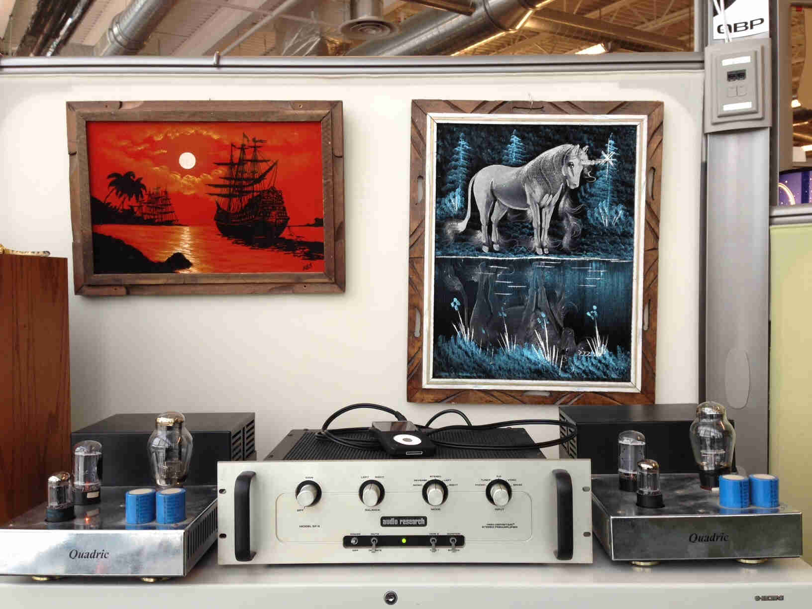 Front view of audio equipment, sitting on a table in an office cubicle, with framed paintings on the wall behind it