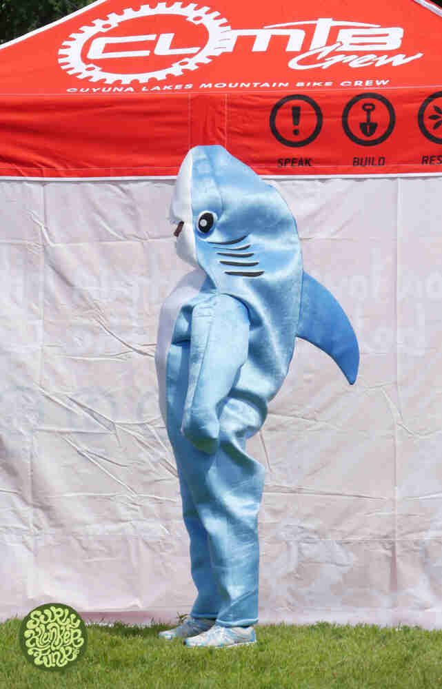 A person wearing a shark costume, standing next to a CLMRC canopy