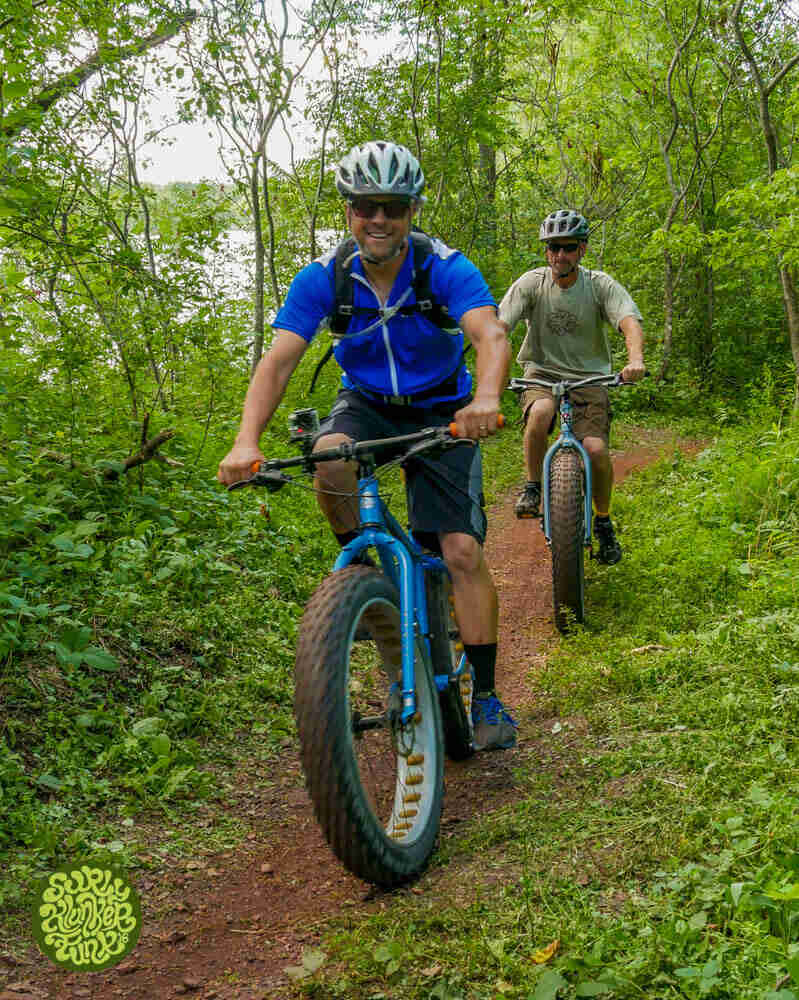 Front view of 2 cyclists riding Surly fat bikes, on a dirt trail in the woods