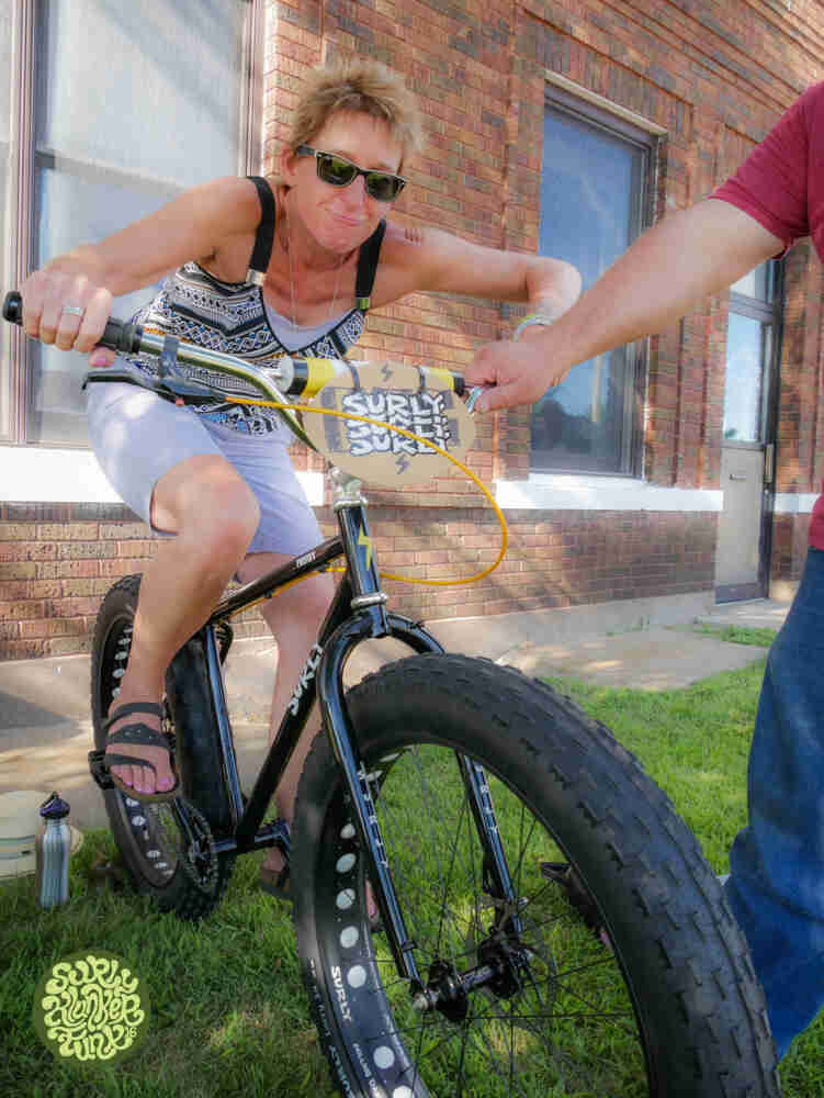Front view of a cyclist on a Surly Pugsley fat bike, next to a building, with a person holding them up by the handlebar