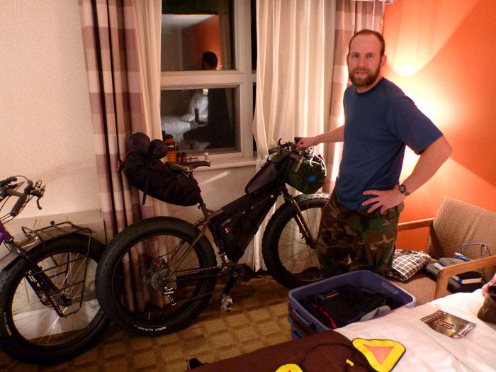 Right side view of a Surly Moonlander bike fat bike with gear, against a motel room wall, with a person standing near