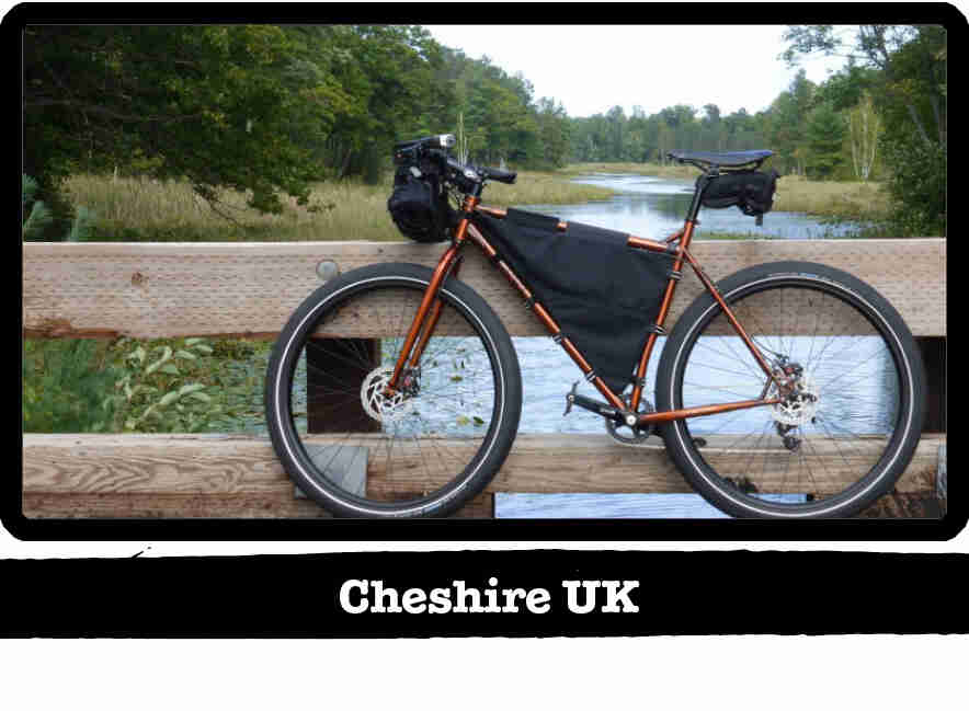 Left profile of a Surly Karate Monkey bike, copper, in front of a wood bridge rail - Cheshire UK tag below image