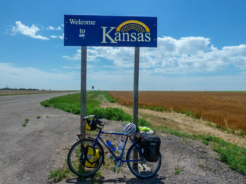 Left side view of a blue Surly bike loaded with gear, on the side of a roadway, under a Welcome to Kansan sign