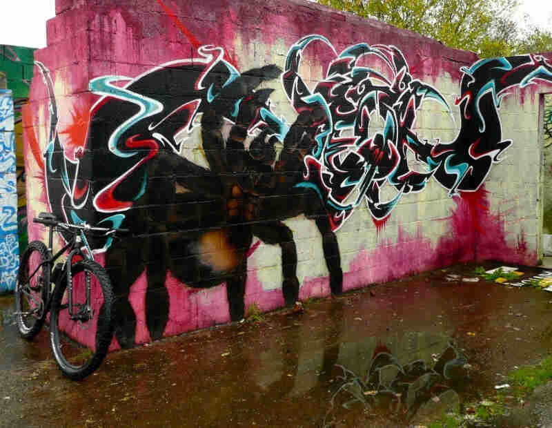 Front, right side view of a Surly bike, parked on corner of cinder block walls, with graffiti painted on the front wall