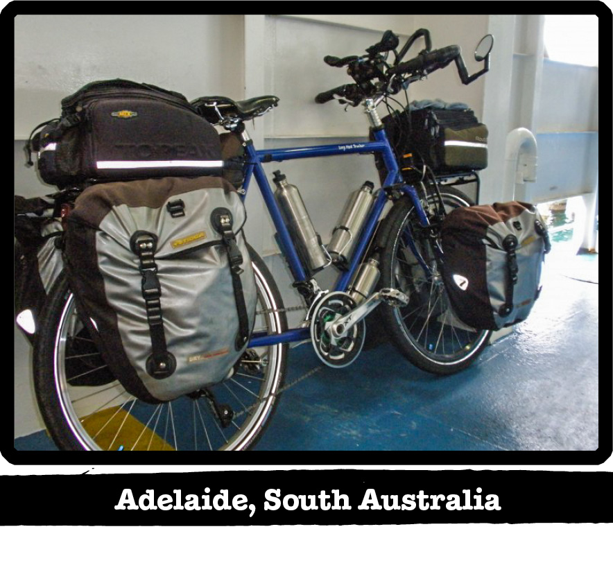 Right side view of Surly bike,blue, loaded with gear leaning on a wall-Adelaide, South Australia banner below image