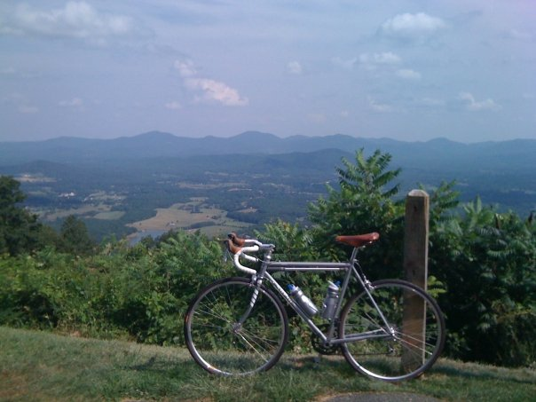 Left side view of a Surly Pacer bike, white, on the grass at an overlook with trees and mountains behind