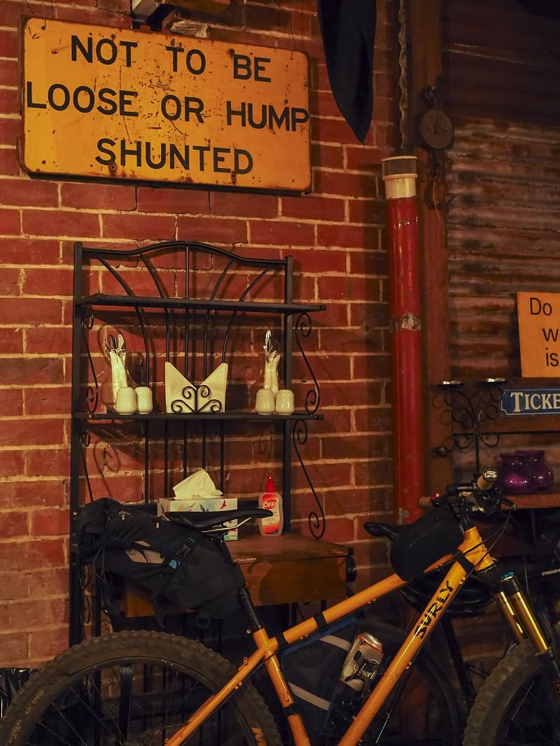Right side view of a yellow Surly bike in front of bakers rack, sign against a brick wall
