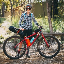 Right side view of a red Surly bike with gear packs and a cyclist standing behind, in the woods