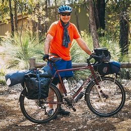 Right side view of a dark red Surly bike with gear packs and a cyclist standing behind, in the woods