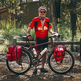 Right side of a Surly bike with red gear packs, and a cyclist standing behind, in the woods