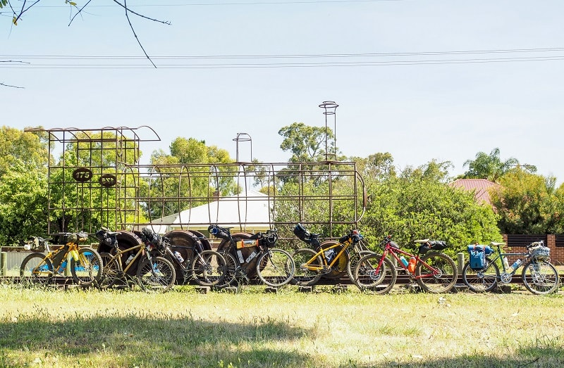 Right side view of bikes in a single file line with a railroad track and steel tube train sculpture with trees behind