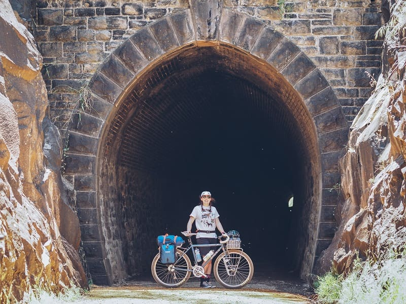 Cyclist standing behind a bike loaded with gear, shown in a right profile, at the entry to a mountain tunnel
