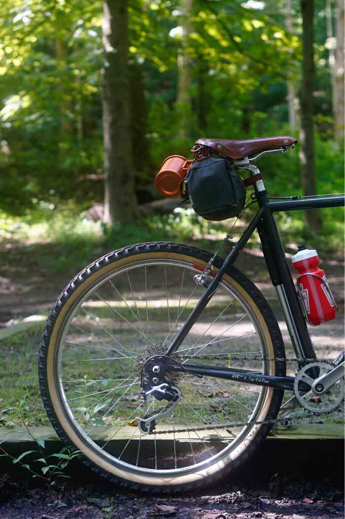 Right side view of the back half of a Surly Pack Rat bike with gear in the woods