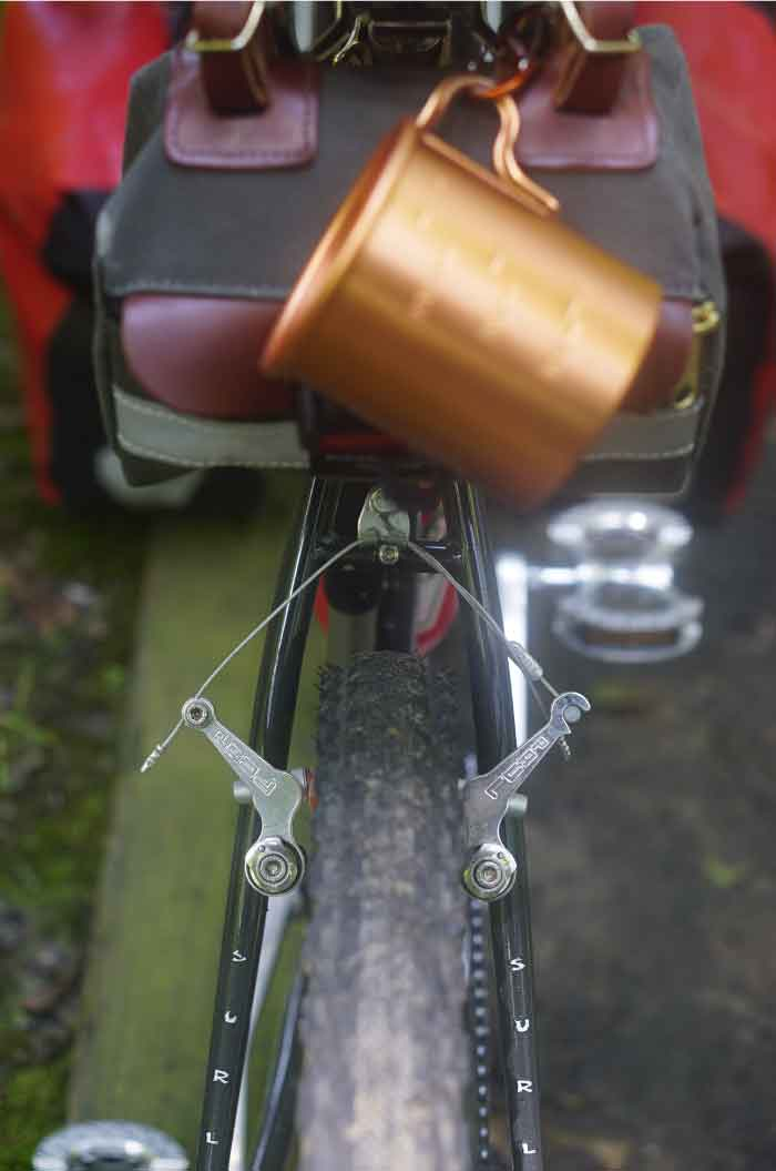 Rear end of Surly Pack Rat bike showing seat stay with brake and tire sporting a seat bag with cup
