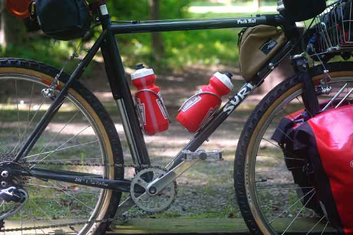 RIght side view of a Surly Pack Rat bike loaded with gear from the top tube down on a gravel trail in the woods