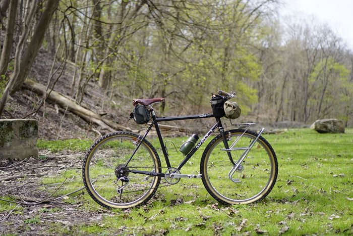Right side view of Surly Pack Rat bike in the grass with a tree covered hill to the left