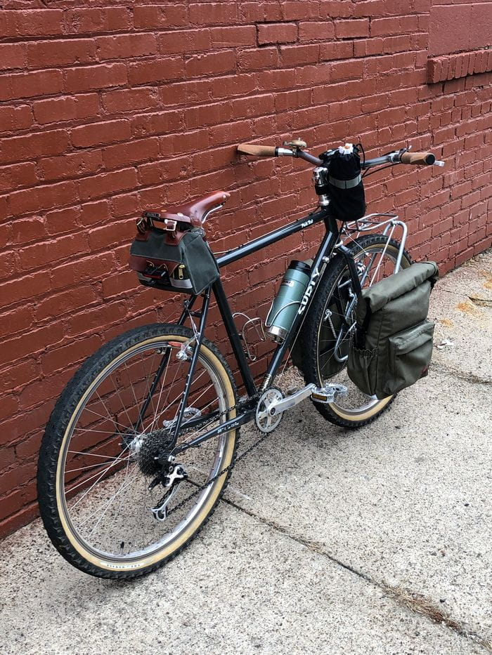 Right angled view of Surly Pack Rat bike loaded with gear leaning on a red brick wall of sidewalk