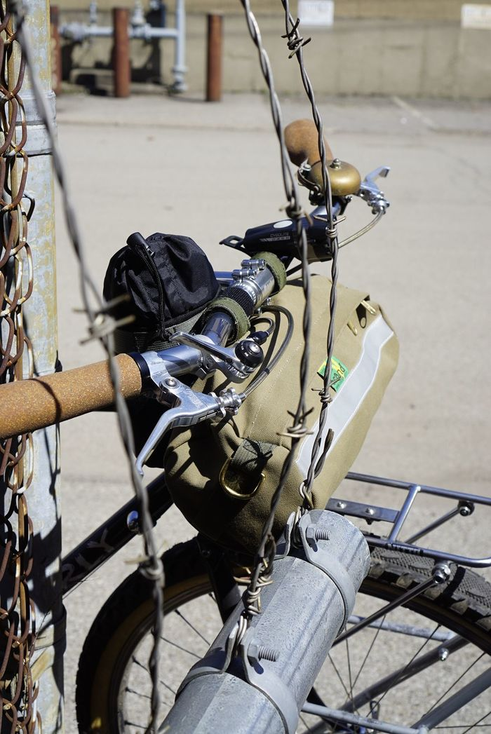 Right side view of Surly Pack Rat bike handle bars with storage bag with barbed wiring wrapped around them