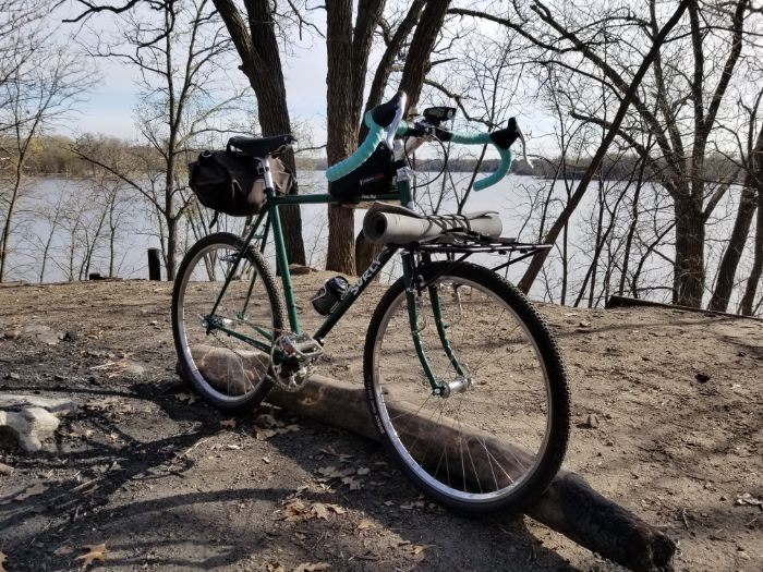 Angled front side view of a green Surly Rat Pack bike standing upright on a dirt clearing with trees and lake behind