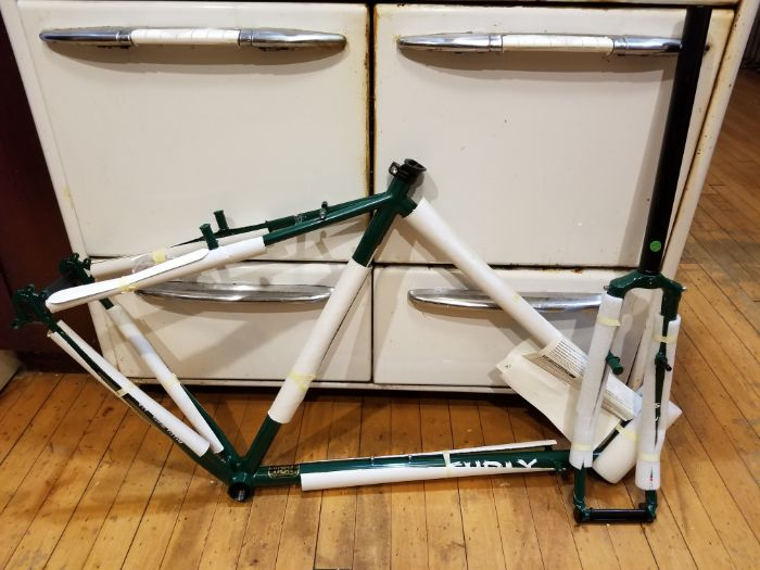 Right side view of a wrapped Green Surly Pack Rat frame and fork leaning against a white 4 draw cabinet on a wood floor