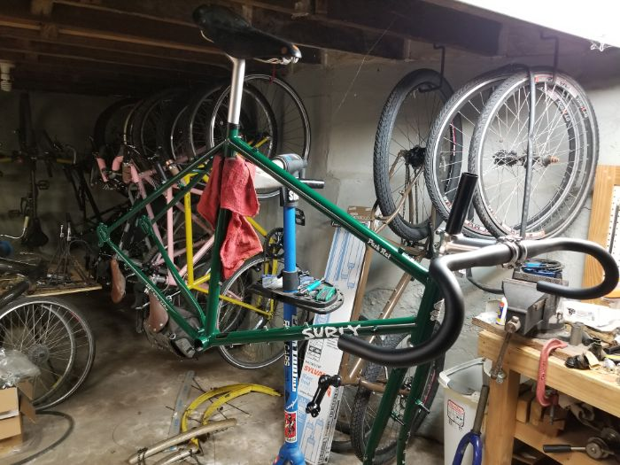 Ride side view of a green Surly Rack Rat bike frame with various parts on a repair stand in a basement with bikes and parts