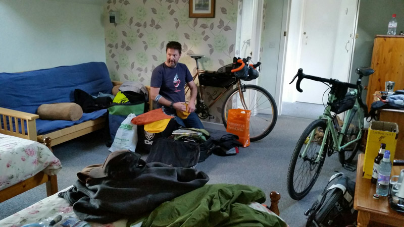 A person sitting in a chair in a room with gear scattered around and 2 bikes