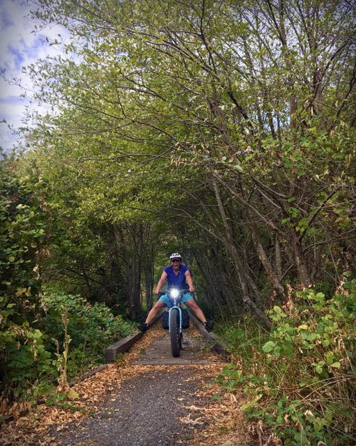 Cyclist rides over trail bridge in the woods with legs outstretched to the sides of a Surly Ice Cream Truck fat bike