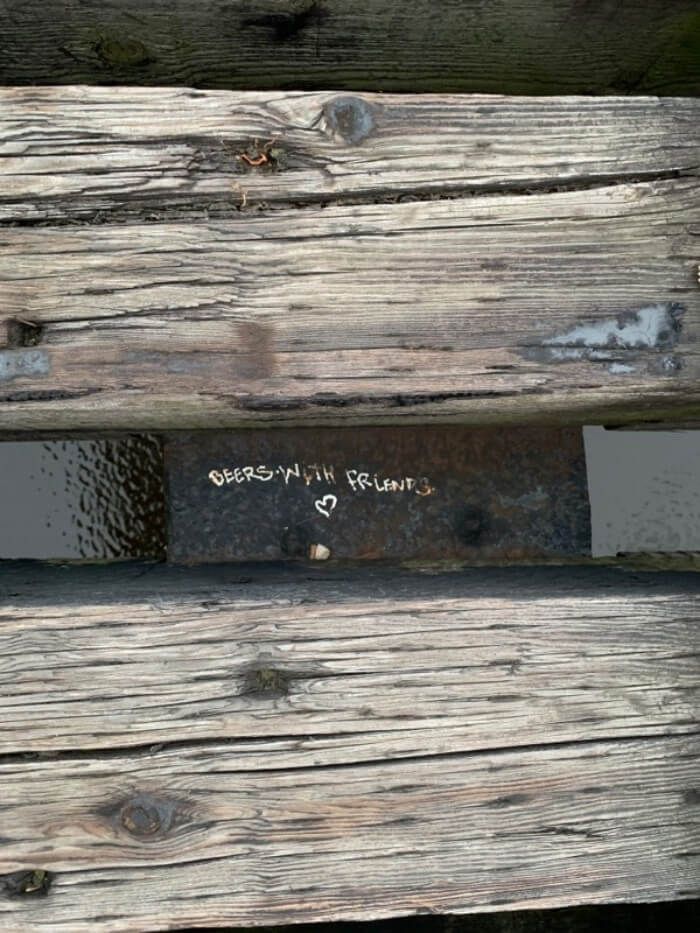 Metal plate with the words 'beer with friends' and heart written in white between to railroad ties