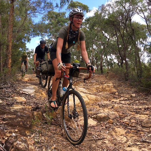 Three cyclist in a row riding down a rocky trail hill in the woods