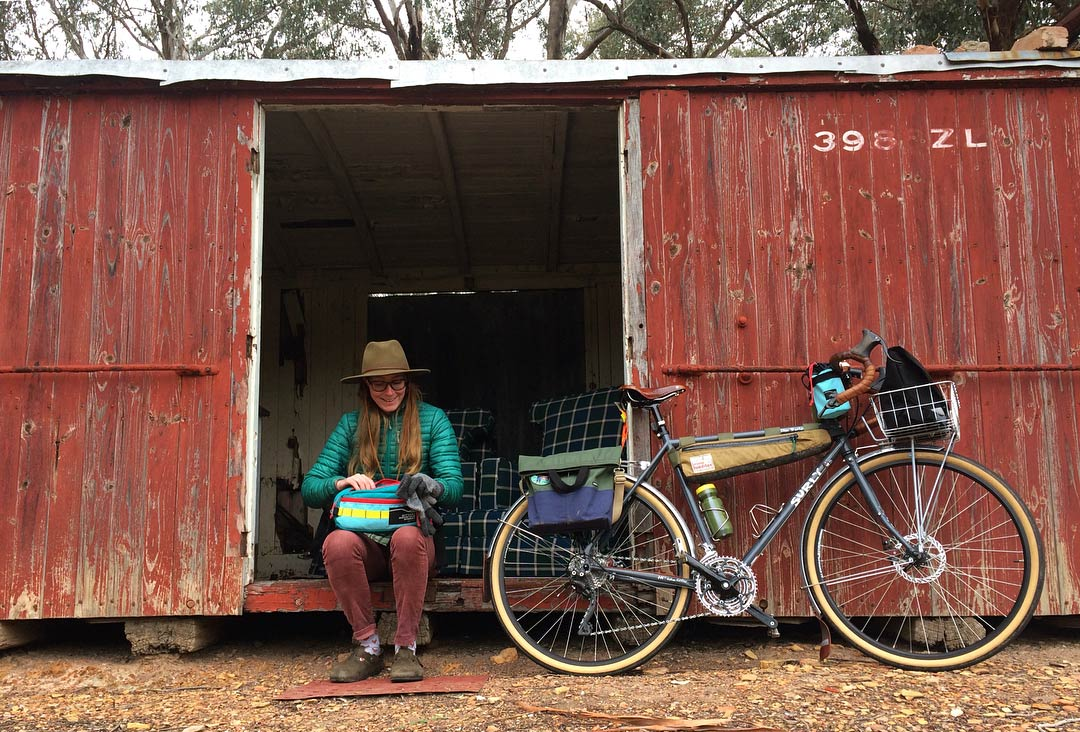 Person sitting at the door  opening of a red steel shed with their Surly bike next to them