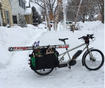 Right profile view of a tan Surly Big Easy bike with rear saddle and skis in the snow with trees and house in background
