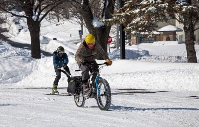 Cyclist riding a fat bike towing a skier down a snow covered street in a neighborhood with trees