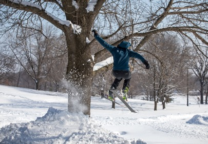 Skier in a hooded blue coat flys through the air near a tree after launching from a jump in a snow covered field